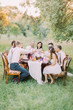 The wedding dinner is arranged in the spring sunny wood by the happy newlywed couple and their guests.