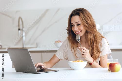 Foto op Plexiglas Sap Smiling woman using laptop while eating breakfast