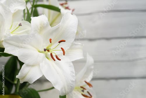 Białe lilie na jasnym tle drewnianych