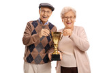 Elderly man and elderly woman holding a golden trophy