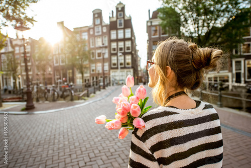 Papiers peints Amsterdam Woman enjoying great view on the buildings holding a bouquet of pink tulips in Amsterdam city