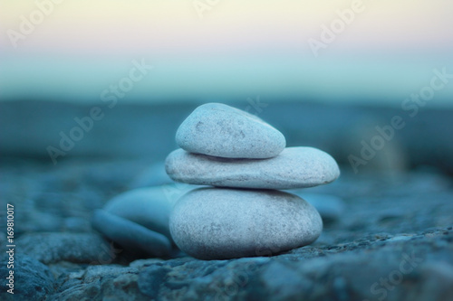a pyramide of zen stones on the rocky beach during sunset Poster