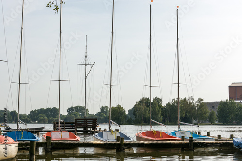 Sailing boats at a wooden pier on a lake Poster
