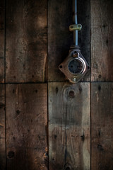 Antique socket box on wooden wall of abandoned barn.