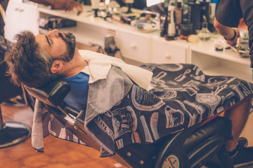 Man with beard sitting on the chair at barbershop.