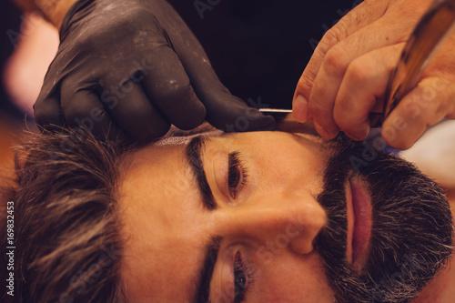 Bearded man getting his beard cut at barber shop.