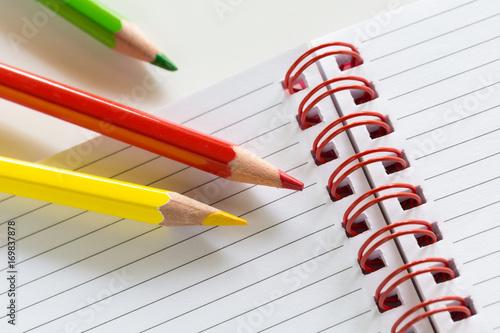 Pastelowa czerwień, zieleń i żółć na paski notatki z czerwoną spiralą