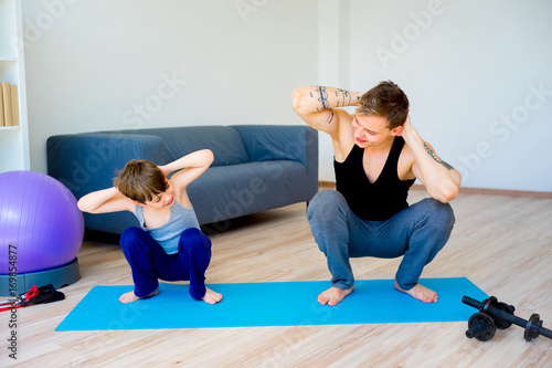 Father and son doing squats together