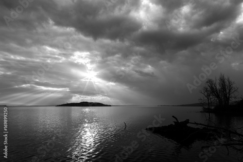 Aluminium Schipbreuk Sun rays coming out through the clouds over an island on a lake, with trees and trunks in the foreground