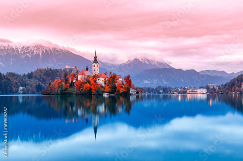 Fotobehang Lichtroze Bled lake in Slovenia, famous and very popular landmark and travel destination. Night scene of island with ancient church in the middle of Bled lake. Romantic place, sunset dusk scenery. Fall season.