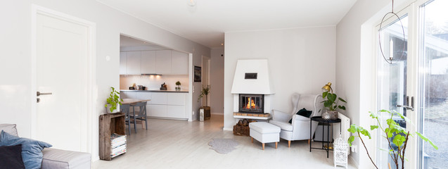 panorama of a cozy living room with lit fireplace, glass doors,