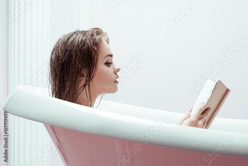 woman reading book in bath tube