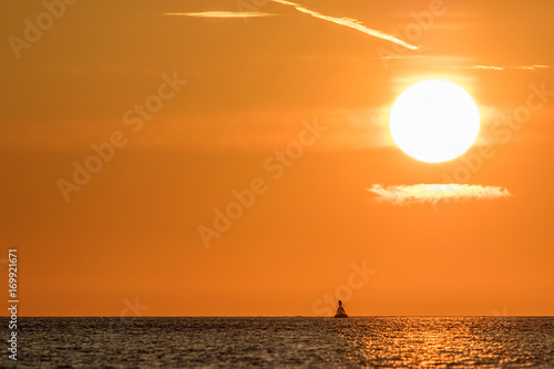 In de dag Oranje eclat Zen sky. Beautiful sunrise with clear orange sky above calm sea and solitary buddha shaped buoy.