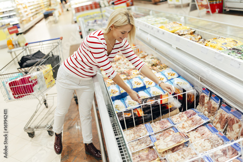 Beautiful woman buying food in supermarket