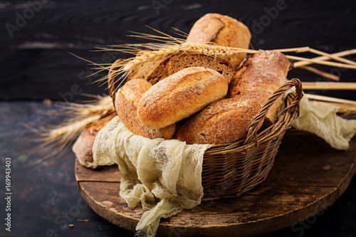 Poster Assortment of baked bread and bun on a wooden background