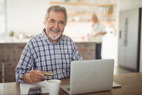 Smiling senior man paying bills online on laptop in kitchen