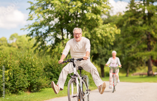Leinwandbild Motiv happy senior couple riding bicycles at summer park