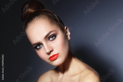 Young beautiful woman with orange lips and hair bun