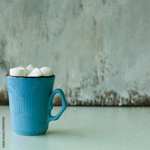 Foto op Plexiglas Chocolade hot chocolate with marshmallows in a blue mug on a wooden table, square, copy space