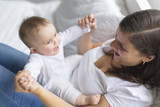 happy loving family. mother playing with her baby in the bedroom. - 169964665