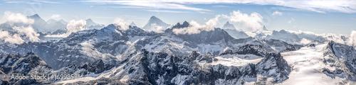 Leinwanddruck Bild large panorama sur une chaîne de montagne enneigées des Alpes suisses