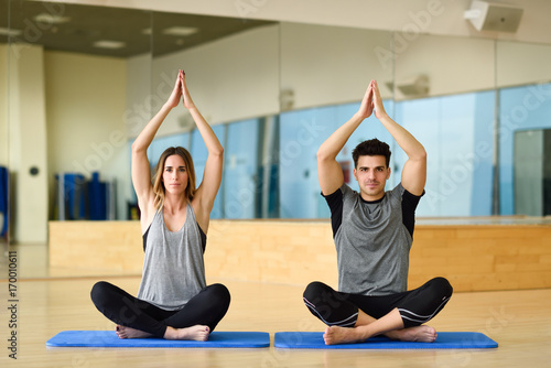 Poster Young woman and man practicing yoga indoors
