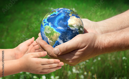 Leinwandbild Motiv The man gives planet Earth to baby. Ecology concept. Elements of this image furnished by NASA