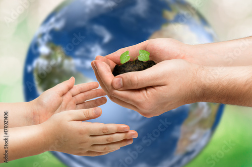 Foto Murales Father gives a little sprout to the baby. Planet Earth as background. Ecology concept. Elements of this image furnished by NASA