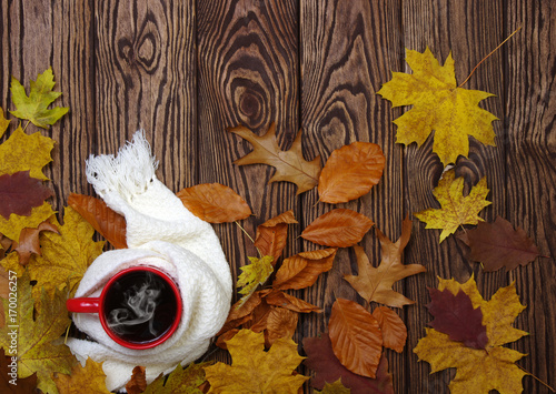 Hot cup of coffee and a scarf on wooden table background