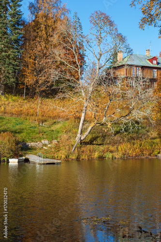 Fotobehang Pier Manor house on a hill by a lake and forest in autumn colors