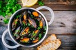 Delicious seafood mussels with with sauce and parsley.  Lemon and baguette . Clams in the shells.
