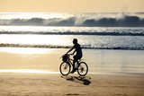 Girl on a bicycle is riding along the ocean at sunset - 170046260