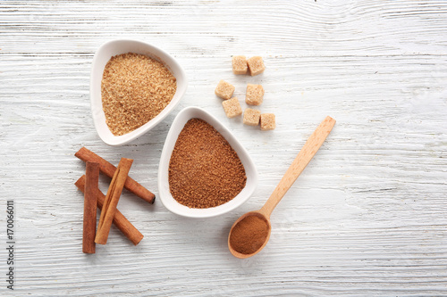 Fotobehang Kruiden 2 White bowls with cinnamon sugar and sticks on wooden background