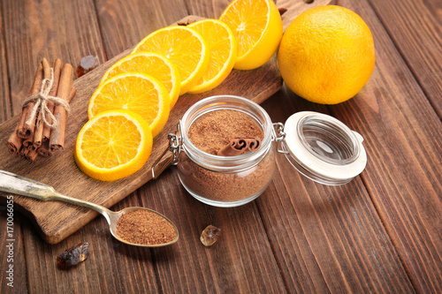 Fotobehang Kruiden 2 Composition with cinnamon sugar in glass jar and orange slices on wooden background