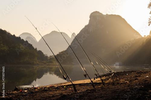 Staande foto Guilin Fishing rods against river at sunset. Idyllic Li River scenery, landscape of Yangshuo in Guilin, China