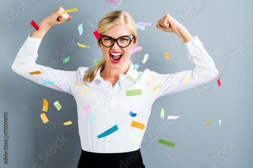 Wall mural Young strong business woman celebrating with confetti