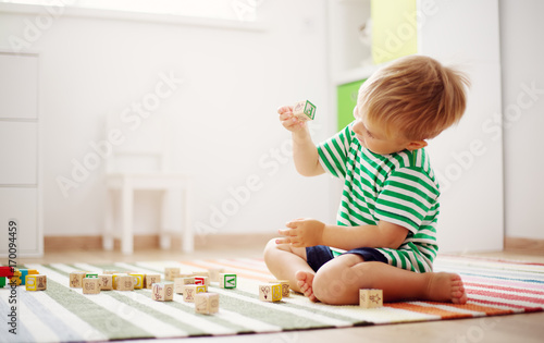 two years old child sitting on the floor with wooden cubes