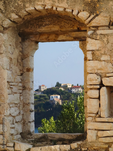 Fototapeta Beautiful view from window made of stones toward Ionian sea and houses on neighboring island in Syvota, Greece