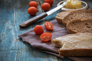 Whole wheat bread, fresh butter and cherry tomatoes on the rustic table