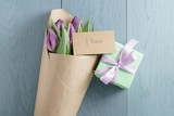 top view of gift with purple tulips in craft paper on blue wood background with 8 march card
