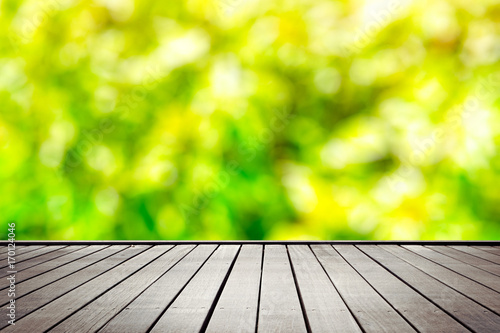 Fotobehang Lime groen Wooden floor perspective and green forest with ray of light, blured with bokeh