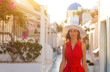 Santorini travel tourist brunette woman in red dress visiting famous white Oia village.