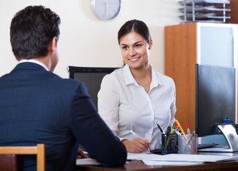 agent listening to customer and smiling in agency