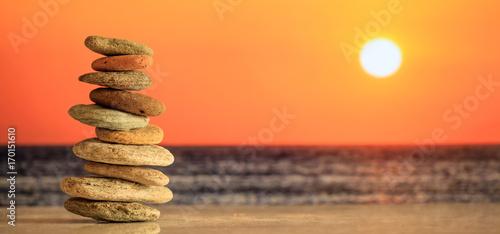 Leinwanddruck Bild Zen stones stack on sea background at sunset