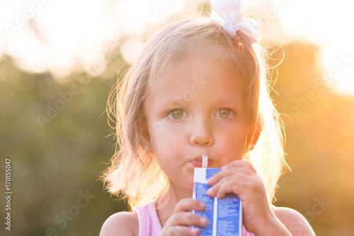 Foto op Plexiglas Sap Girl child drinks juice