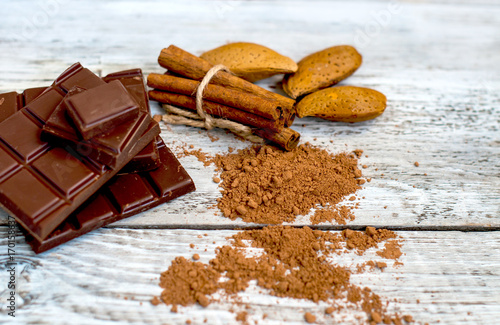 Papiers peints Café en grains a chocolate bar and cocoa powder with nuts on a light background.