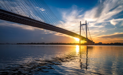 Vidyasagar Setu - the cable stayed bridge on river Hooghly at sunset with moody sky.