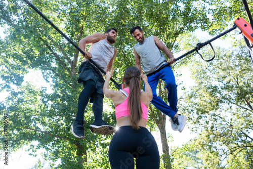 Low-angle rear view of a fit woman showing thumbs up to her two male friends during extreme workout outdoors in a modern calisthenics park