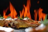 Grilled chicken leg on the flaming grill