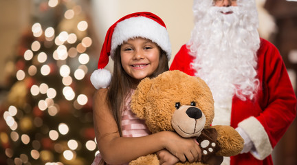 Little girl holding a Christmas present in her house